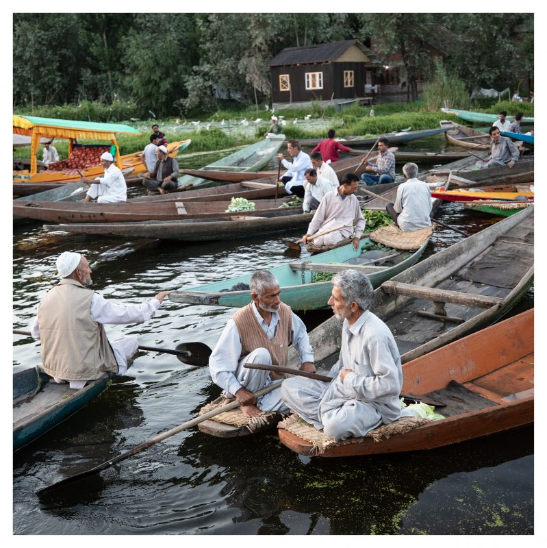 Local Kashmiri men in boats on Dal Lake