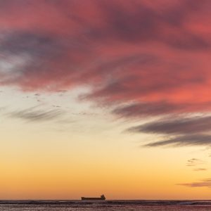 Sunset photo of Point Moore with a pink sky and ship on the horizon